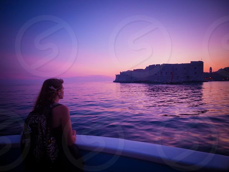 Dubrovnik city walls girl boat travel dusk sea photo