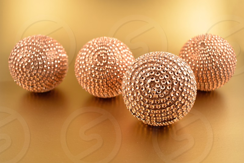Golden Christmas ornament. Christmas balls on a golden background. Elegant holiday background. Shiny gold backdrop with Christmas ball photo