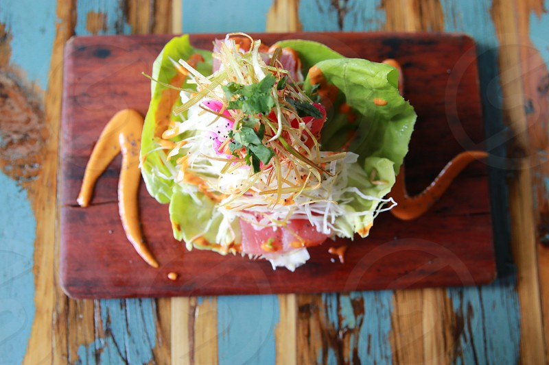 """Dos Santos in Denver Colorado. Pictured here the Raw tuna and pickled onion on a lettuce """"tortilla"""". photo"""