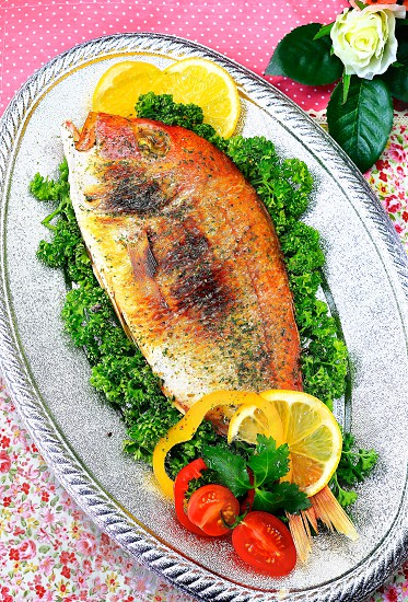 Cooked Whole white fish-pink flowers table cloth background photo