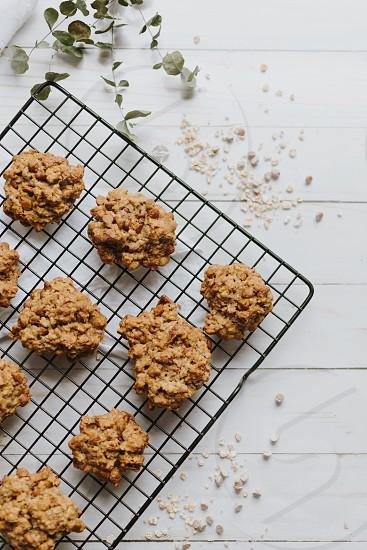 Oatmeal cookies flat lay cooling rack top down messy white wood baking fresh dessert cinnamon minimal minimalist photo
