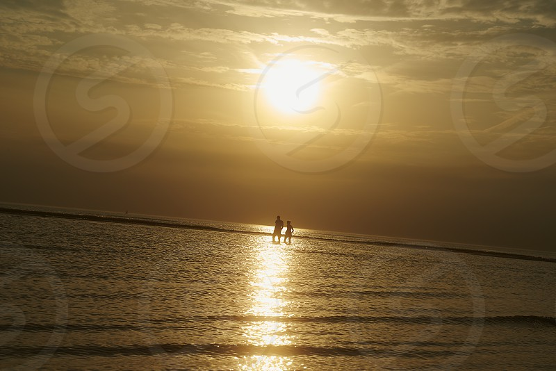 Couple walking in shallow water along the seaside in sunset photo