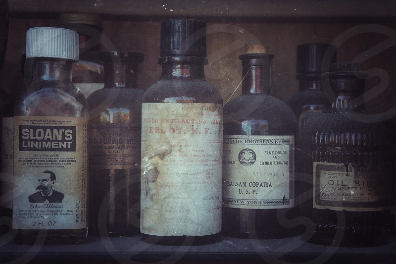 old fashioned ointment bottles on dusty shelf photo