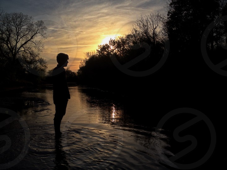 boy standing on river photo