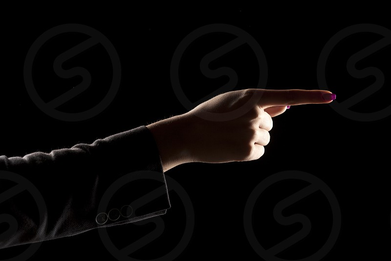 woman's hand on a dark background showing direction photo
