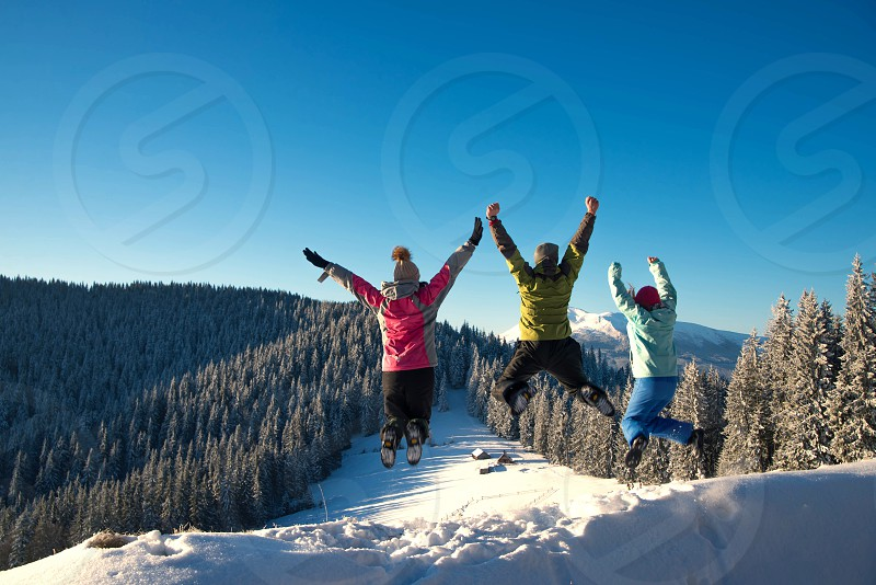Three young friends jumping and having fun on the snowy mountains photo