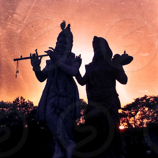 A statue of Krishna & Radha expressing their divine love the silhouette of the sunset behind them forms a glowing heart! (Delhi India) photo