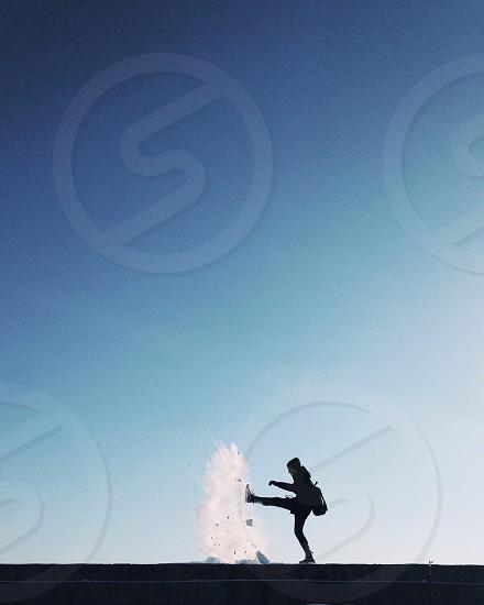 man wearing black knit cap kicking snow under clear blue sky photo