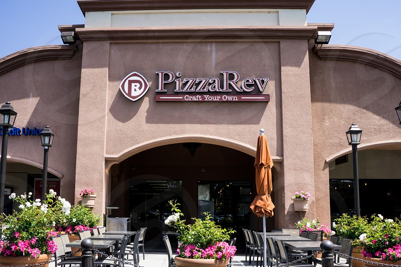 pizza rev restaurant with outdoor table and chairs and brown parasol photo