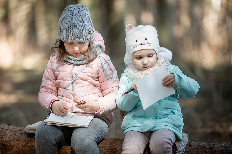 Little sisters  outdoor portrait with sketchbook and pencils. Pencil drawing draw sketch portrait spring winter person education look book painting sisters artists painted business coat charcoal pastel girl kids children child childhood photo