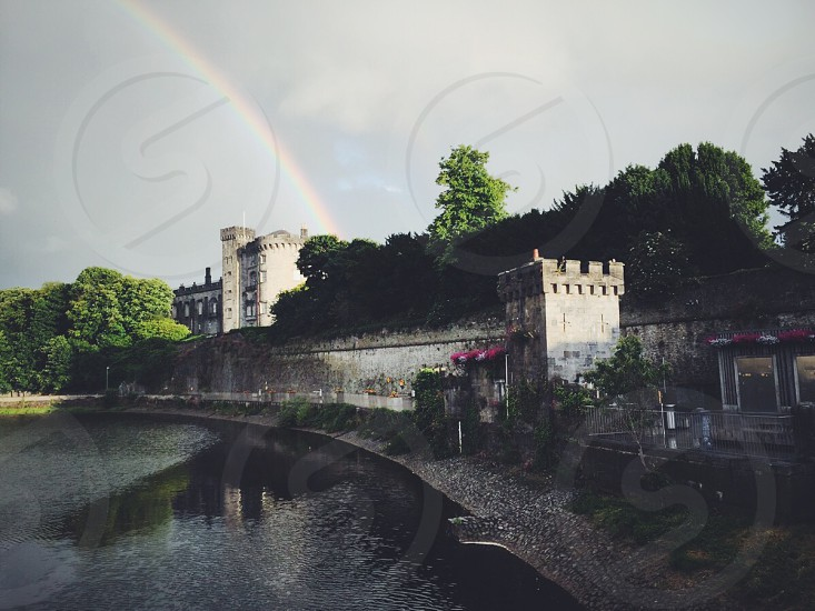 photo of body of water near concrete wall under cloudy sky wand rainbow photo