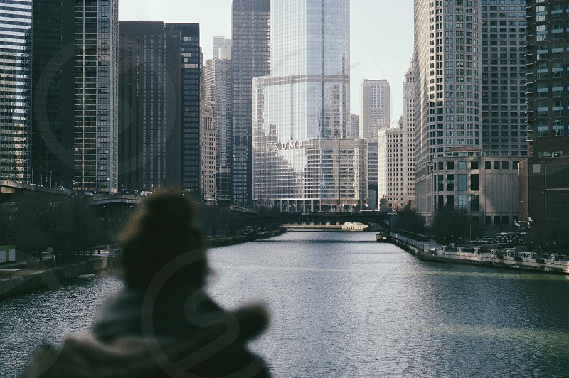 man stands near lake over buildings during daytime photo