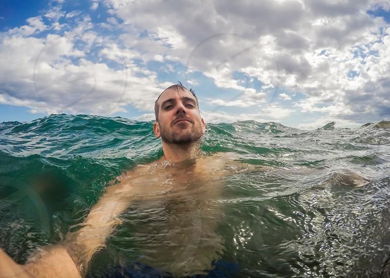Man taking selfie while swimming off of Maui coast. photo