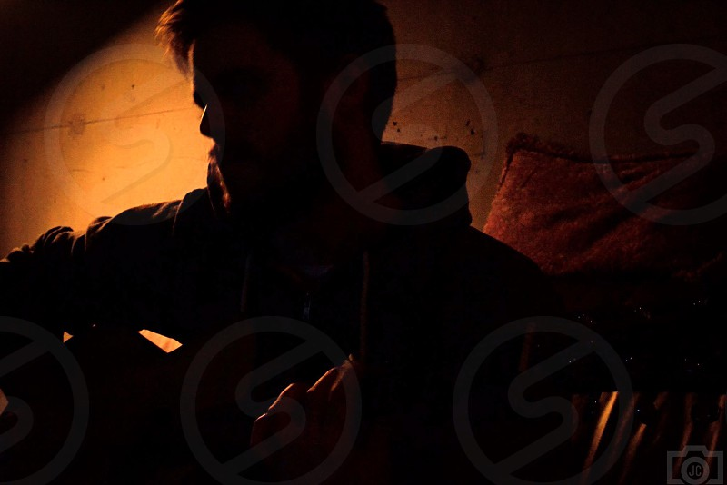 man in black hoodie playing a guitar silhouette photo