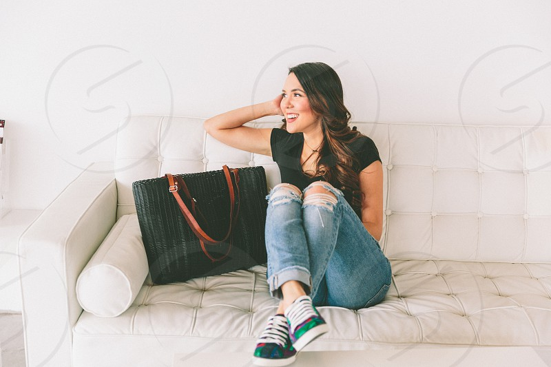 A woman sitting comfortably on the couch.  photo