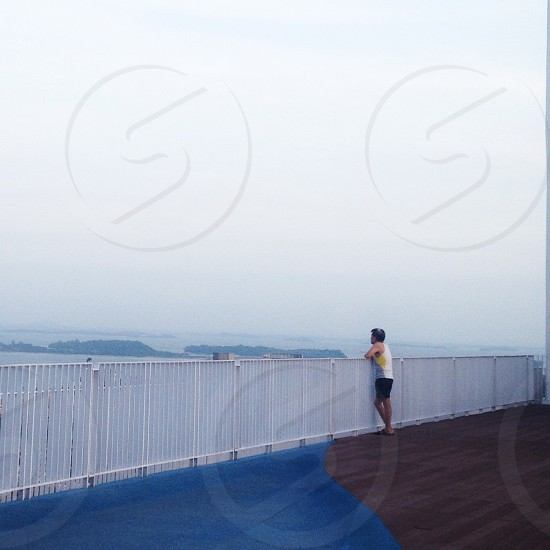 man standing on railing looking out photo