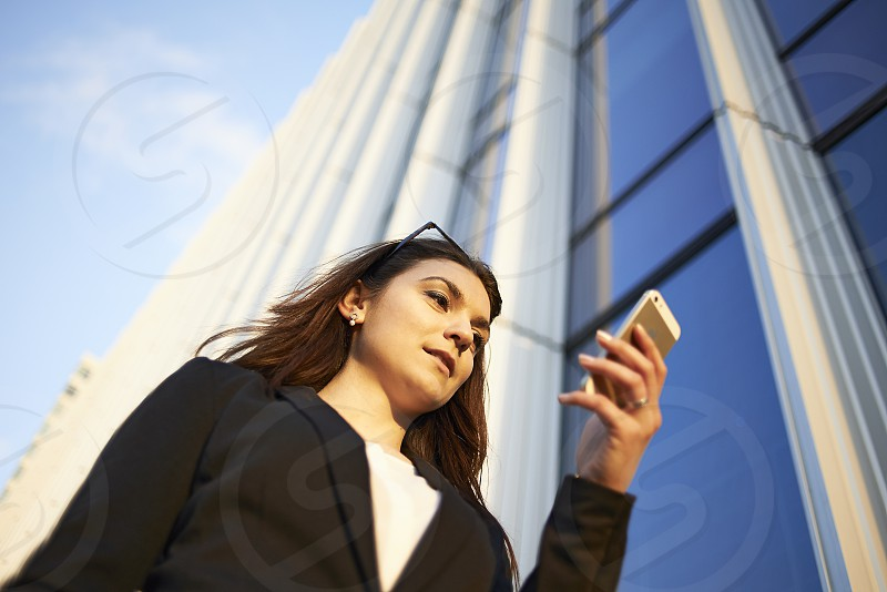 A successful young caucasian woman in business clothing holding a mobile phone standing outside in the business district of the city surrounded by skyscrapers photo