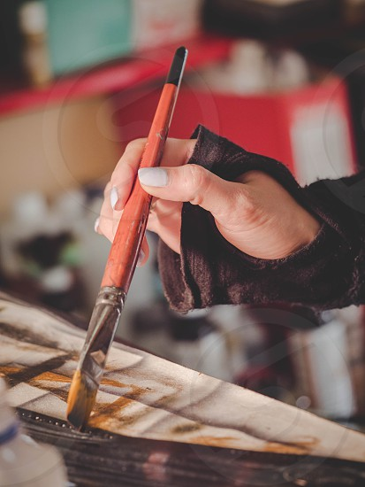 Female artists hand holding big brush. Woman painting picture. photo