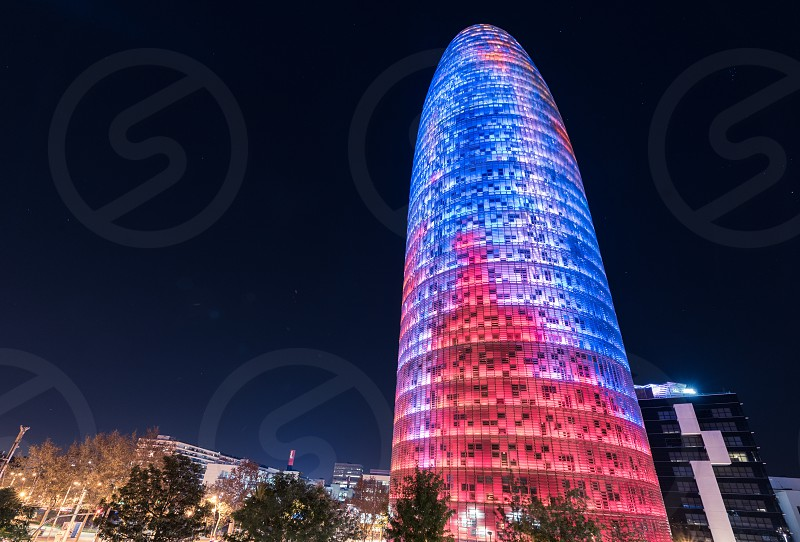The night view of the Torre Agbar.  Skyscraper / tower located between Avinguda Diagonal and Carrer Badajoz near Plaça de les Glòries Catalanes which marks the gateway to the new technological district of Barcelona Catalonia Spain.  photo