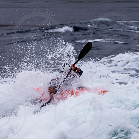 Kayaker mastering whitewater kayaking enjoying the extreme thrill of paddling fast currents  breaking waves and wild water photo