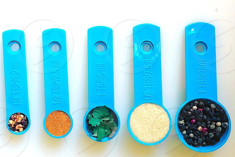 Seen from above on a white background 5 blue measuring spoons contain condiments or spices. photo
