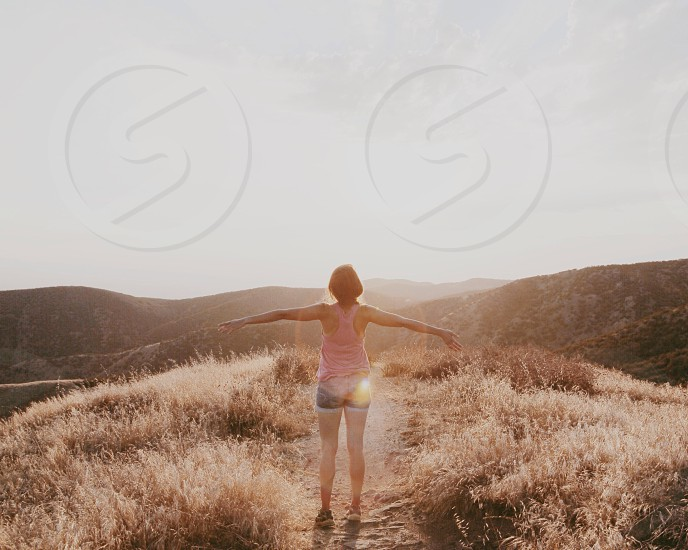 woman in pink tan top with arms spread on mountain trail photo
