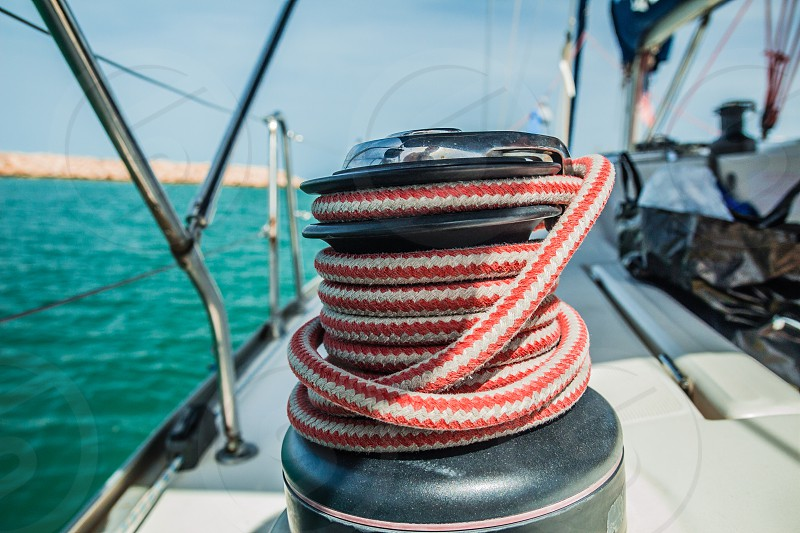 Winch with red and white rope on sailing boat in the sea. photo