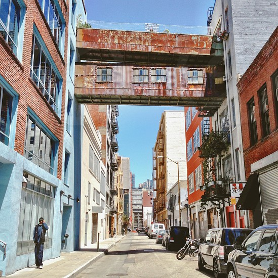 Urban alley with buildings and a man walking alone.  photo