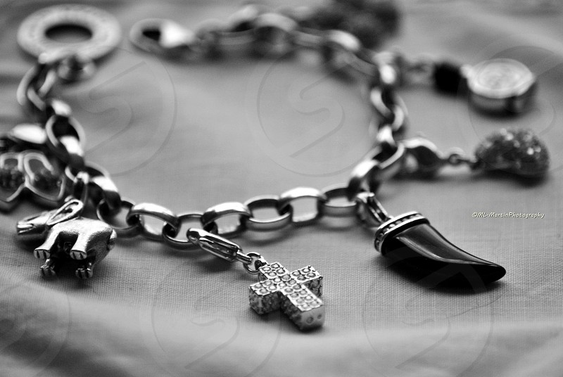 silver cross chain bracelet on white textile in grayscale photography photo