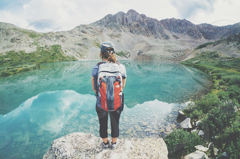 standing brunette woman wearing orange gray white backpack looking at mountain pond photo