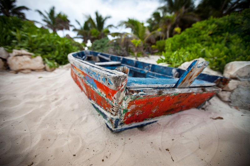 A small weathered rustic row boat / ship / vessel beached on the sandy shore island shows signs of adventure on the seas / ocean / water. photo