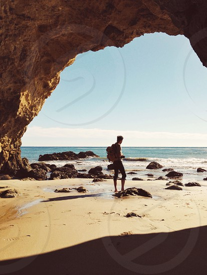 man standing near cave at the shore photo