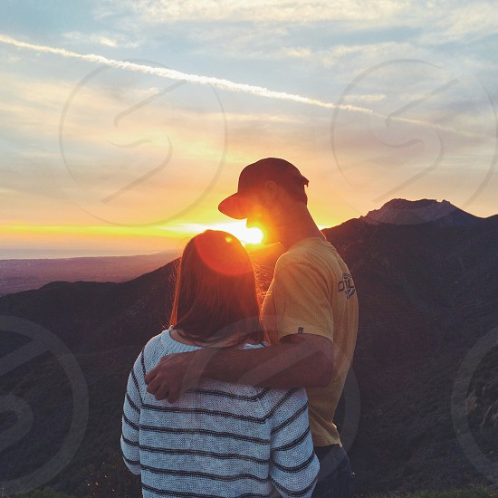 woman and man standing  on top of mountain  photo