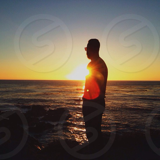man standing on sea side silhouette photo