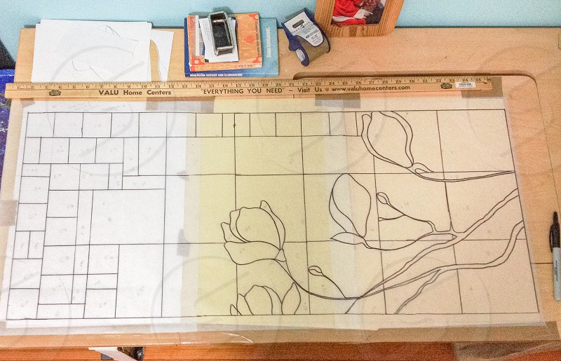 black and white floral design drawing and brown ruler on brown table photo