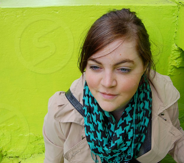 trendy student in front of a bright green wall photo