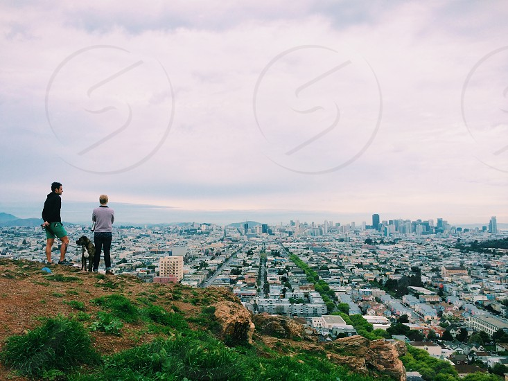 man and woman with dog overlooking city on hill photo