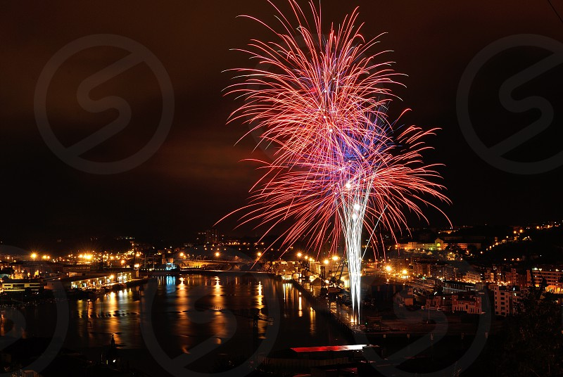 pink silver fireworks display by the pier during nighttime photo