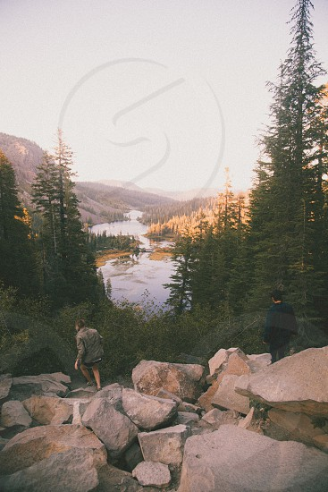 2 people on brown rocky mountain by trees photo