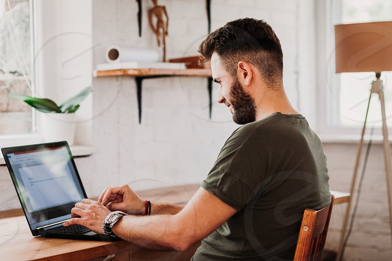 Young casual man working on a laptop photo