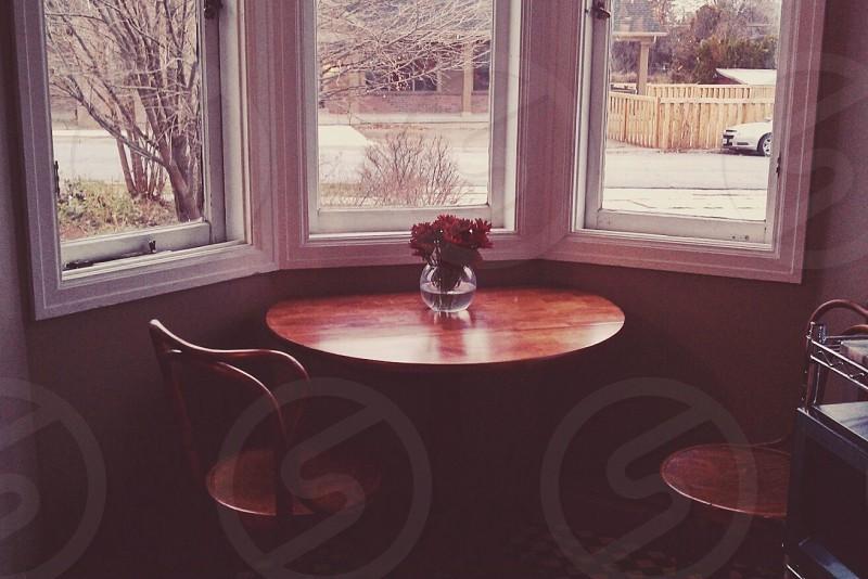 flowers on wood table under windows photo
