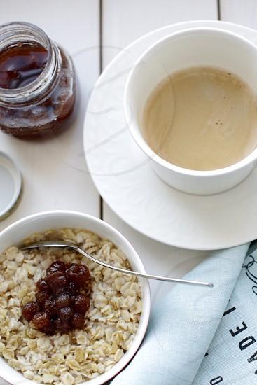 oatmeal on bowl near mug with cream photo