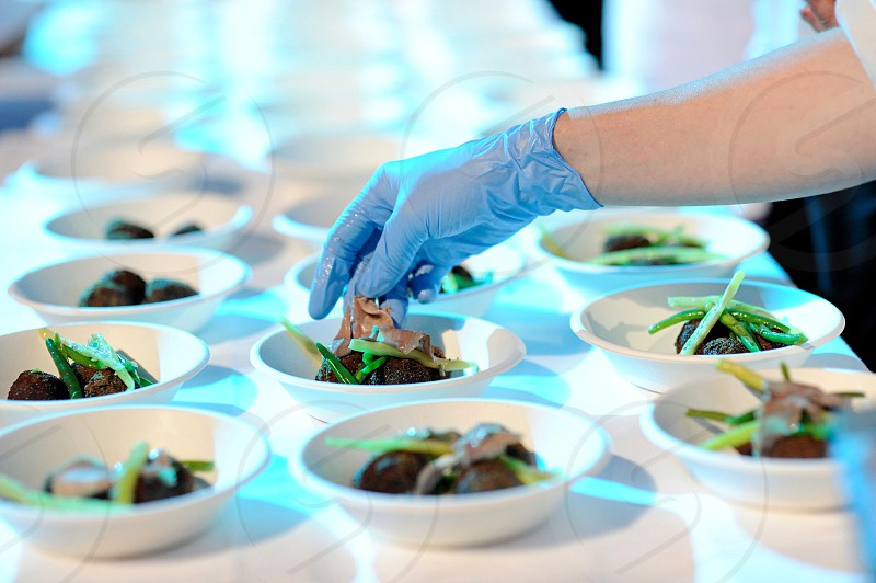 person in white glove fixing foods in bowls on table photo