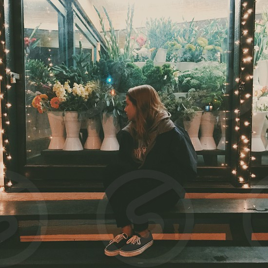 woman wearing black and gray hooded jacket sitting on black steps near white and orange flowers and green leaves in white vases photo
