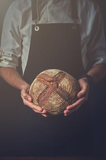 Man hands holding round dark bread blurred background photo