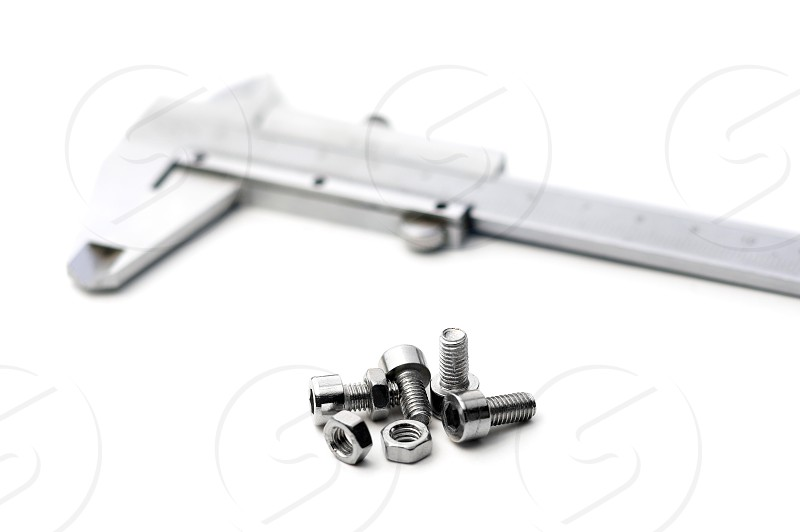 caliper and bolts on white background photo
