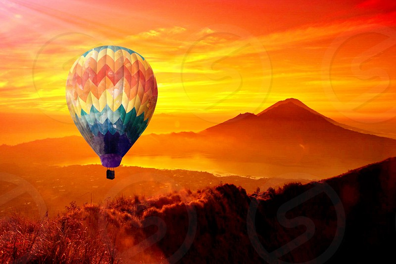 green and yellow orange red hot air balloon flying above mountains under yellow and orange sunset photo