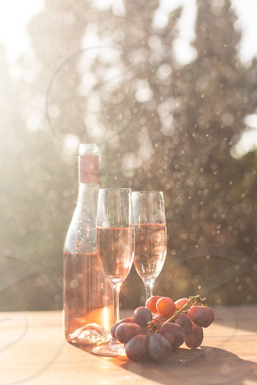 two champagne flutes filled with rose wine next to the bottle and purple table grapes surrounded by trees under the sun photo