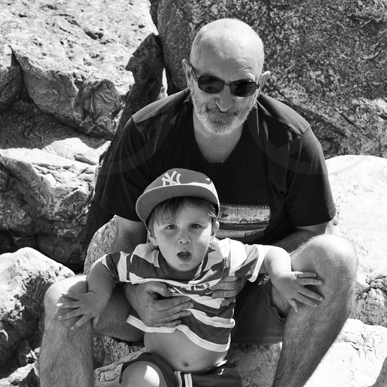 man in black t shirt with boy in striped polo shirt photo