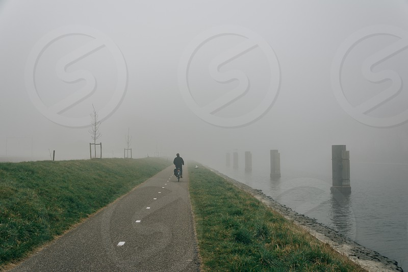 person riding bicycle by the misty bay photo